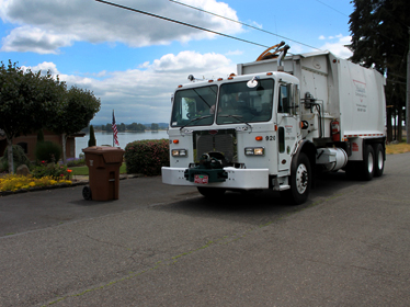 Hudson garbage truck picking up residential recycling.